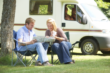 A couple sitting outside an RV with a map